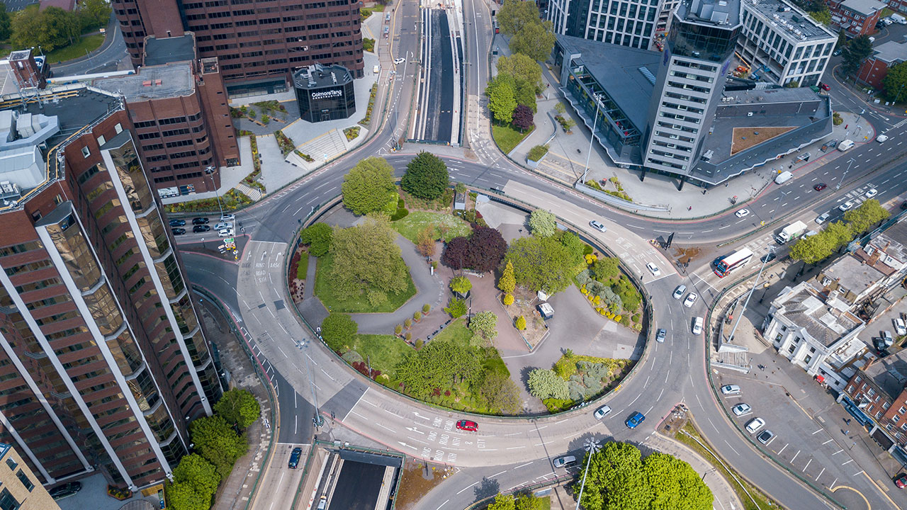 Large roundabout road system viewed from above, with green grass in the middle