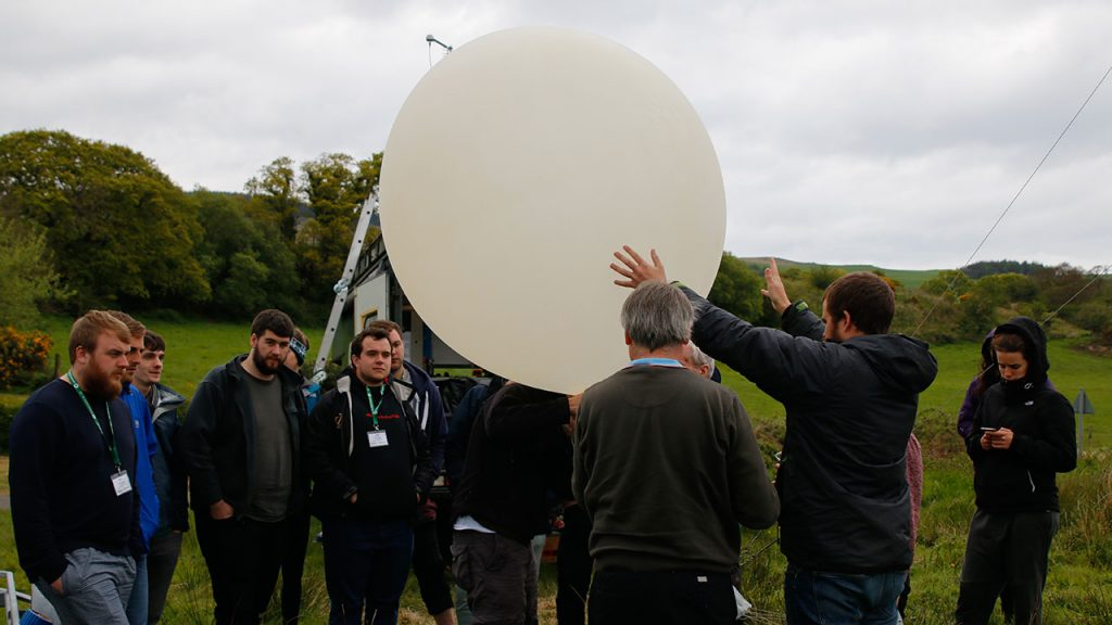 Ten people stand in a circle around a large white balloon filled with gas