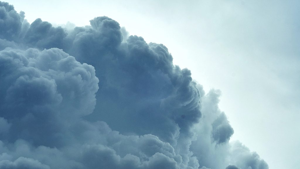 Large fluffy, dark cloud in a blue and white sky.