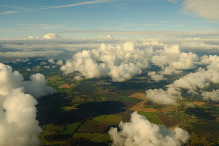 Fluffy, white clouds above green and yellow fields
