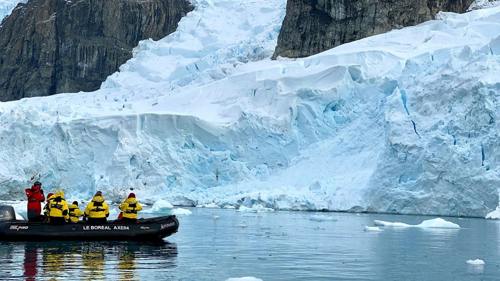Team of people wearing yellow jackets stand on a small black powerboat, they are looking at white sheets of ice in the ocean.
