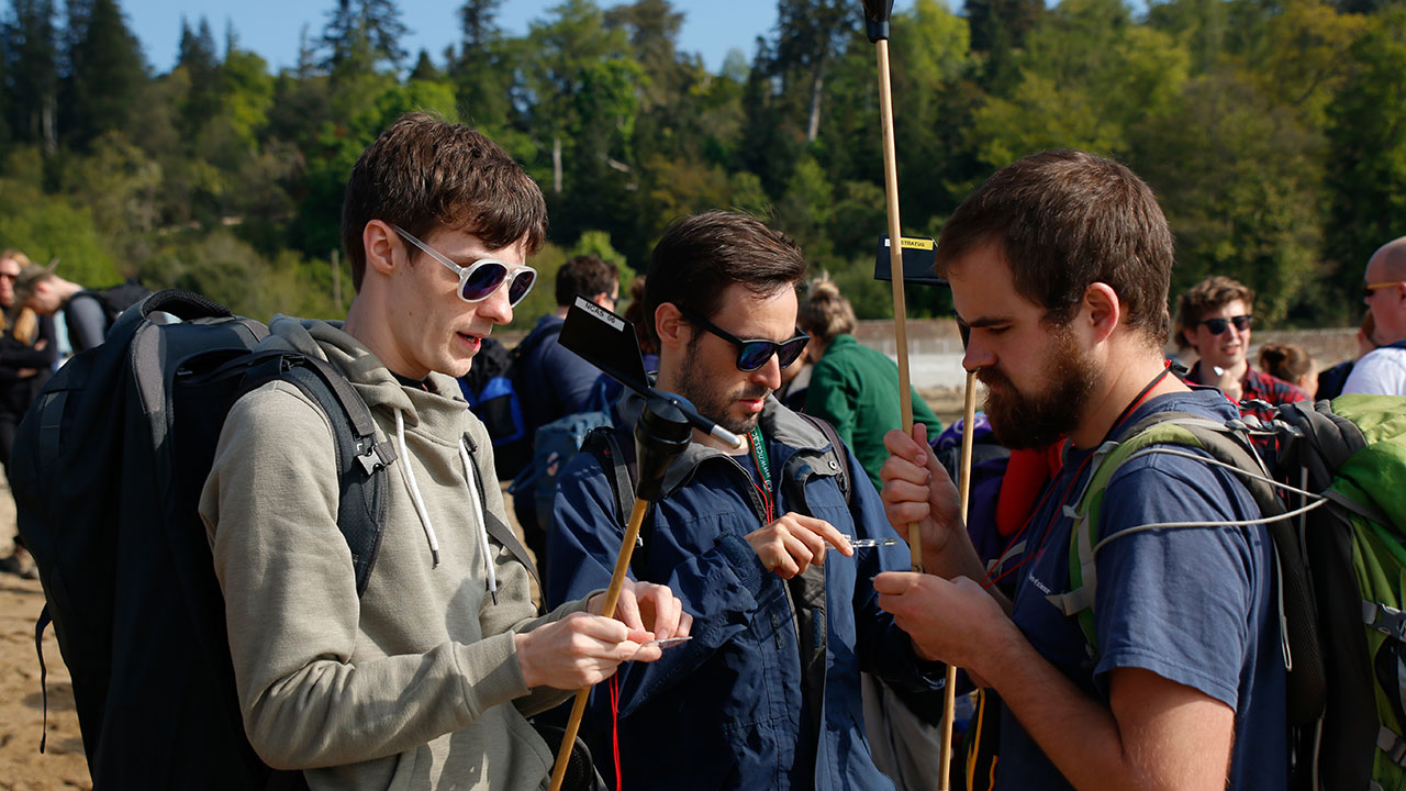 Three men, two wearing sunglasses, look closely at small scientific instruments in their hands
