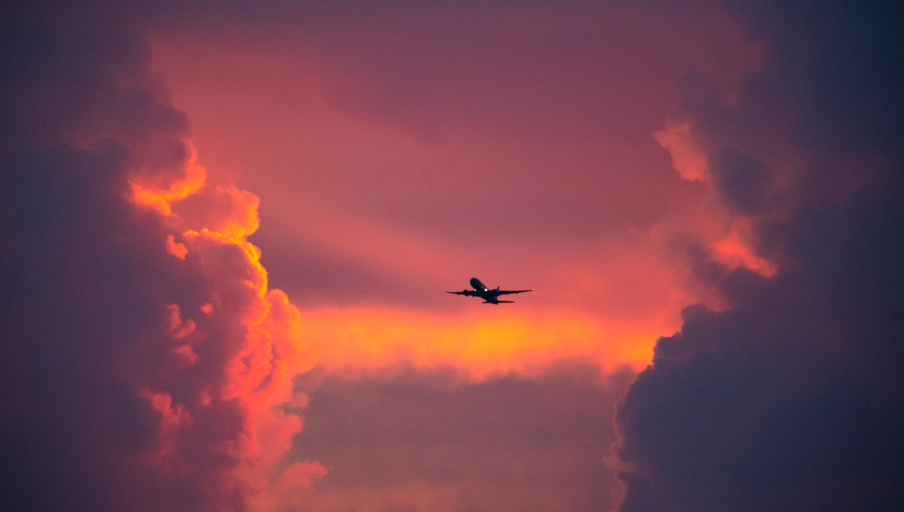 Airplane flying through red hazy clouds