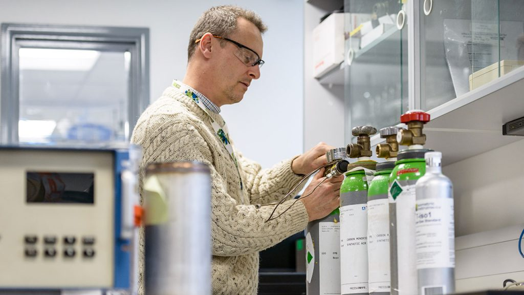 Man wearing beige jumper and safety glasses applies labels to gas canisters on a work bench