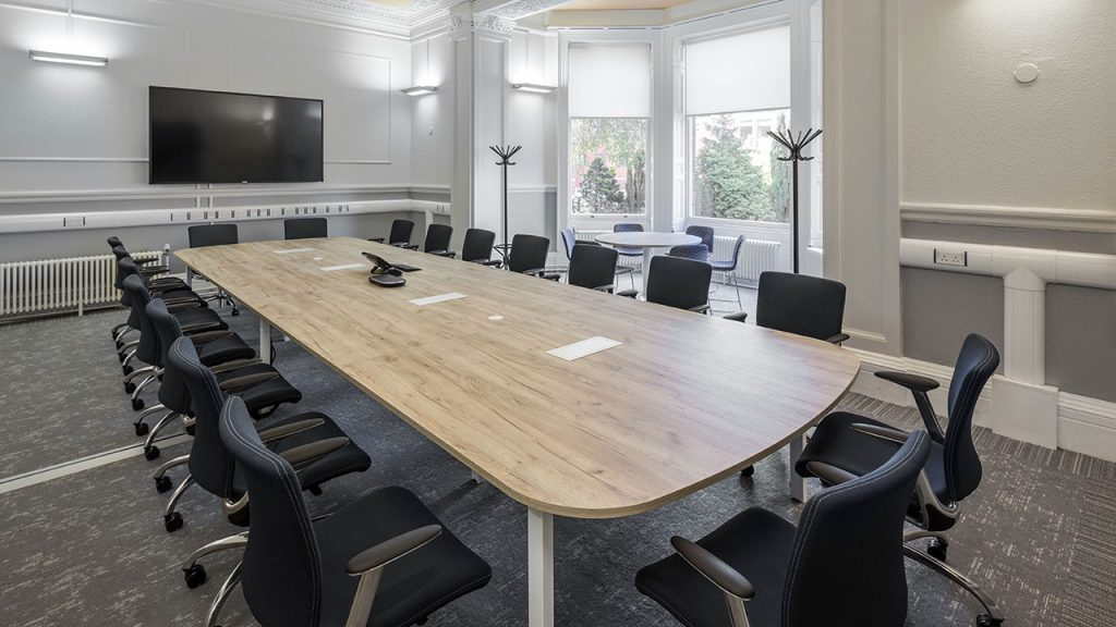 Large wood table with twenty black office chairs around