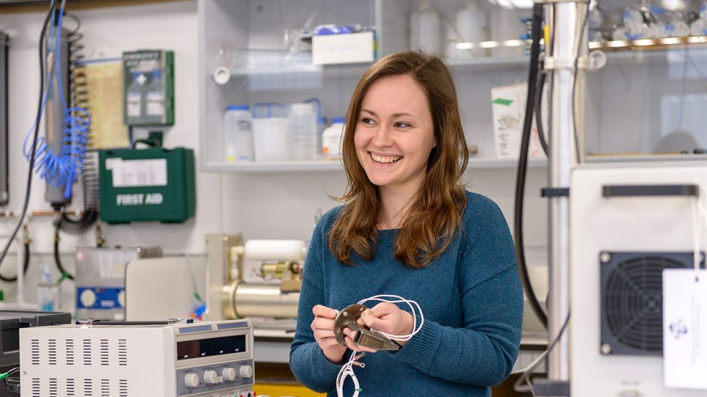 Brown haired woman wearing blue jumper holds cables in her hands in a laboratory