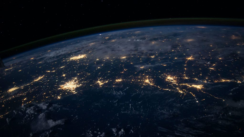 Earth appears as a dark blue sphere in black sky, patches of yellow light represent cities connecting across the earth's surface.