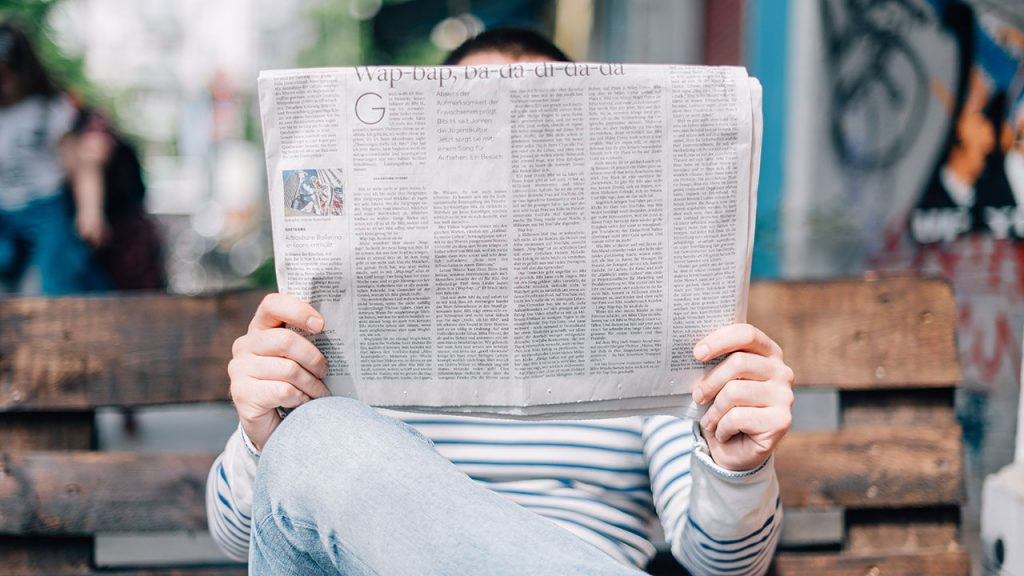 Man wearing jeans sits cross-legged and reads a large broadsheet newspaper