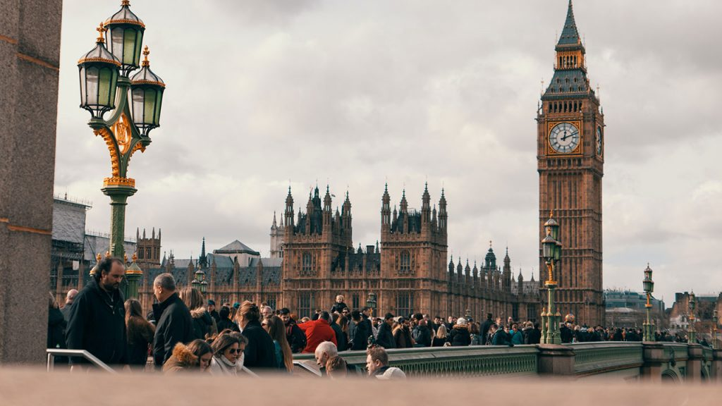 Crowd of people stand in front of large Big Ben tower with clock face at the top