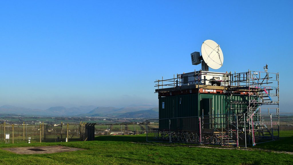 White radar dish sits on top green shipping container in a field, with blue skies behind
