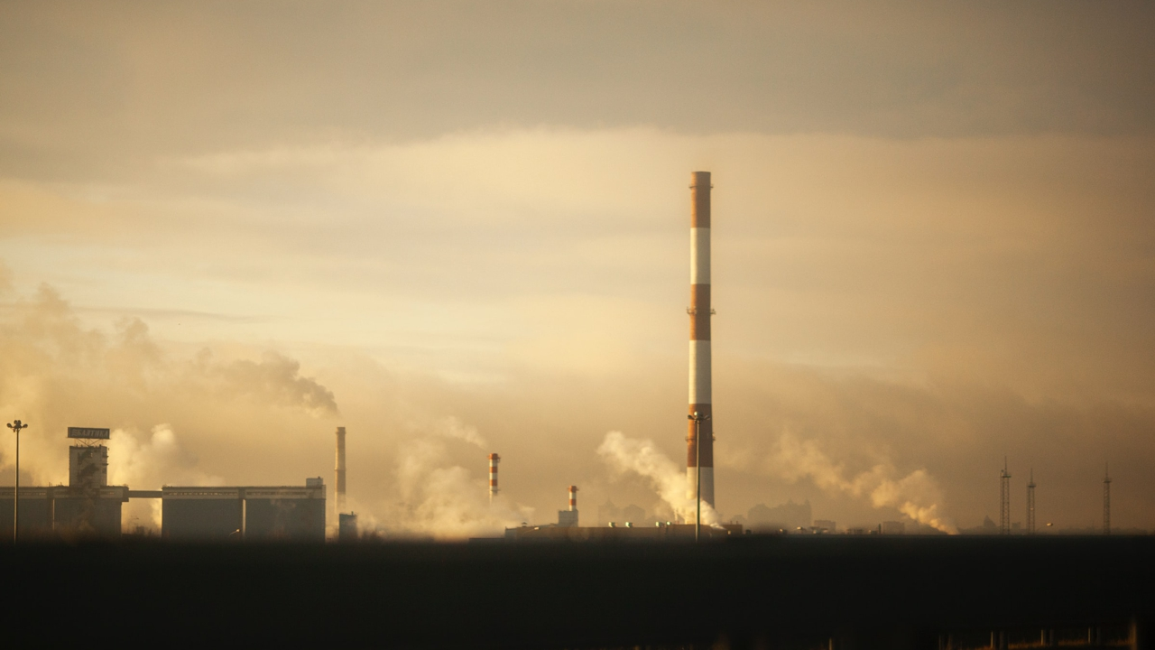 Smokestacks rise from a factory building on the horizon