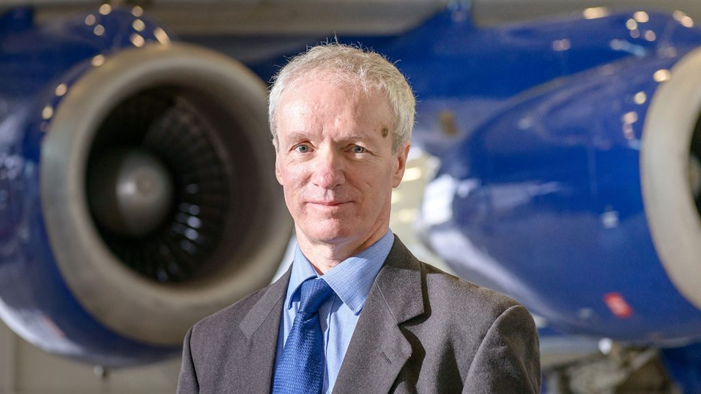 Professor Stephen Mobbs stands, wearing a grey suit, in front of blue aircraft engines