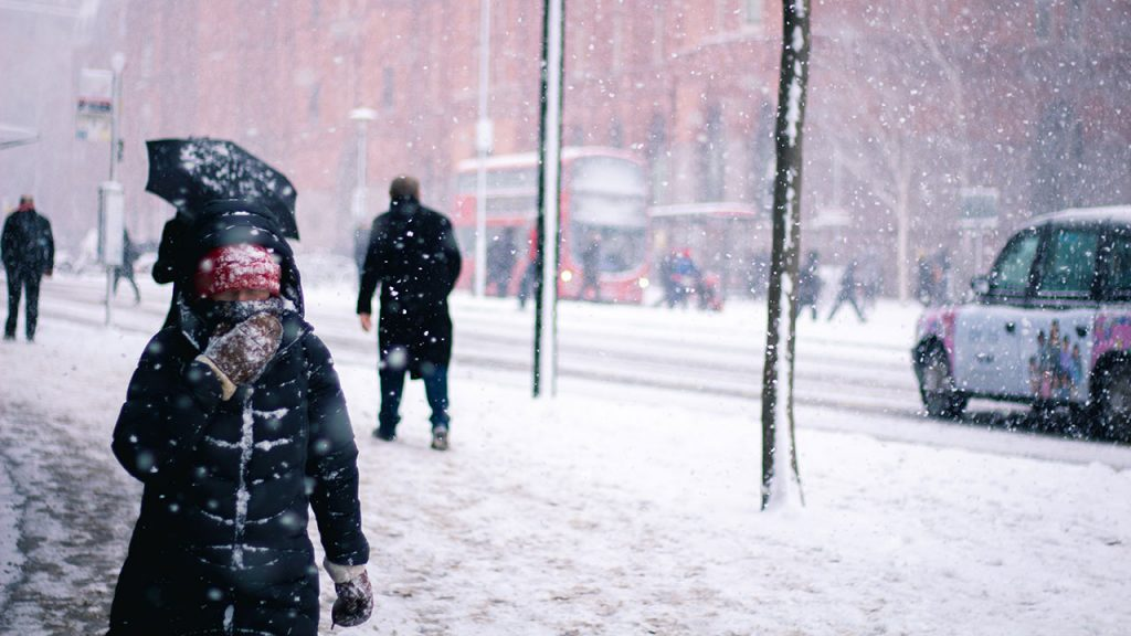 Pedestrians wearing warm coats walk through a blizzard on a snow covered pavement